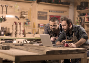 n image of two middle-aged white men in a wood working shop looking at a laptop.
