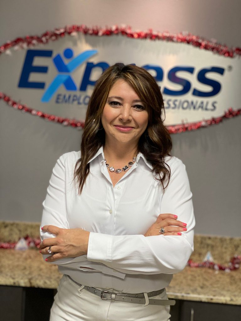 Aracely Melendez stands confidently at the front desk of her Express Employment Professionals franchise.